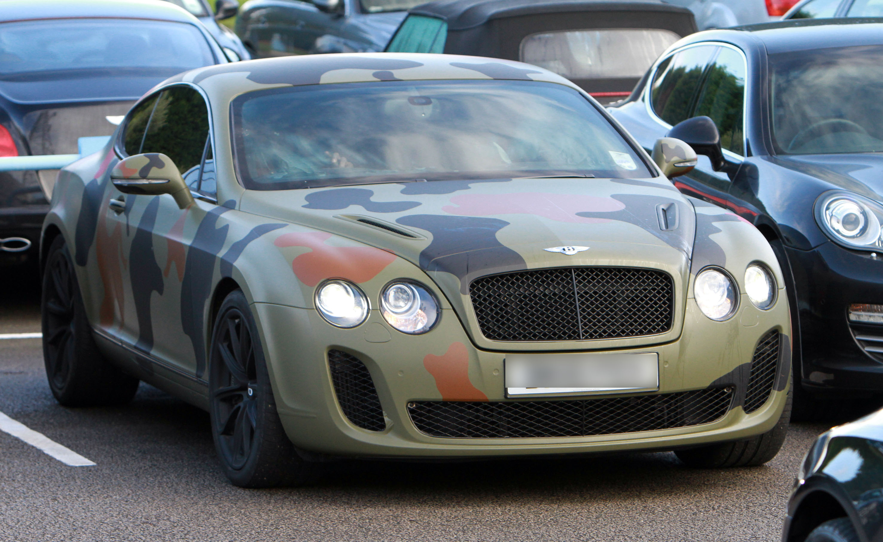 Mario Balotelli with his camouflage car leaving Manchester City training ground
