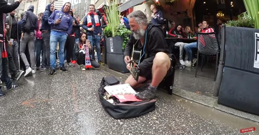 Уникално: Футболни фенове обсипват с монети бездомен музикант (ВИДЕО)