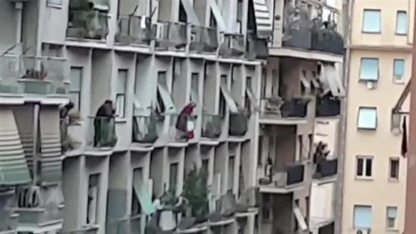 Италианци пеят заедно по балконите, за да повдигнат духа си